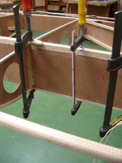 First we thought about doing both sides at once. But I feared major problems with sliding sticks. Luckily we didn't do both. Those sticks slide on that glue! Here you can also see that we use clamps to hold the ends of TWO sticks. Saves a lot of clamps!